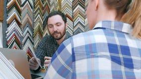 Arbetare för ung man som pratar med kunden om detaljer för bildram, genom att använda bärbar datordatoren på räknare i atelier Fotografering för Bildbyråer