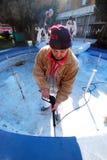 Arbetare förbereder springbrunnen för ny målarfärg Arkivfoto