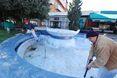 Arbetare förbereder springbrunnen för ny målarfärg Arkivbilder