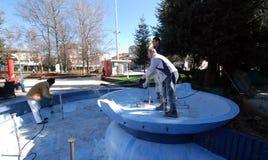 Arbetare förbereder springbrunnen för ny målarfärg Royaltyfri Foto