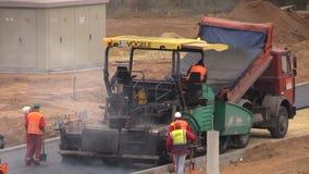 Arbetare fördelade varm asfalt på den nya vägen i bostads- område arkivfilmer