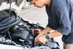 Arbetare f?r f?r man som eller automatisk mekaniker kontrollerar det bilmotoroljan och underh?llet, innan att resa f?r s?kerhet arkivbild