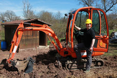 Arbetare framme av en grävskopa royaltyfria bilder