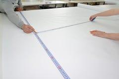 Arbetare g?r en markering p? en PVC-film Shoppa p? produktion av elasticitetstak royaltyfri bild