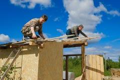 Arbetare gör ett tak i ett landshus arkivbild
