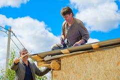 Arbetare gör ett tak i ett landshus royaltyfri foto