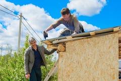 Arbetare gör ett tak i ett landshus royaltyfri fotografi
