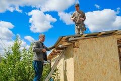Arbetare gör ett tak i ett landshus royaltyfria foton