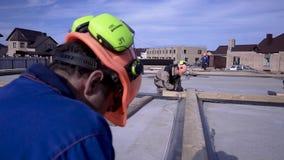 Arbetare gör mätningar som mäter bandet på konstruktion gem Byggmästare i likformign och den hårda hatten som arbetar på konstruk arkivfilmer