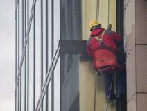 Arbetare gör ren byggnadsfasaden Arkivbild