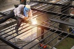 Arbetare gör ståltak målade svart arkivbild