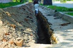 Arbetare gräver ett hål i asfalten på fot- avsnitt royaltyfri bild
