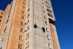 Arbetare hänger advertizingen på en byggnad royaltyfri fotografi