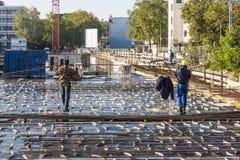 Arbetare hjälper det bärande byggnadsmaterialet för kranen till consten Arkivbild