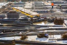 Arbetare hjälper det bärande byggnadsmaterialet för kranen till consten Arkivfoto