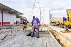 Arbetare hjälper på jordning, den mobila kranen är bär cementtjock skiva Royaltyfria Bilder