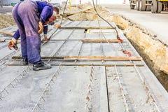 Arbetare hjälper på jordning, den mobila kranen är bär cementtjock skiva Arkivbilder