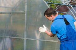 Arbetare i blåa likformig som kontrollerar den korrekta installationen av växthuset och polycarbonaten på den fotografering för bildbyråer