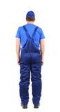 Arbetare i blåa overaller. Tillbaka sikt. Arkivbild