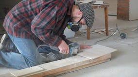 Arbetare i en plädskjorta och keramiska tegelplattor för respiratorsnitt med en vinkelmolar stock video