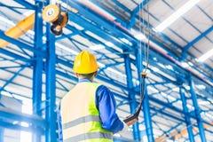 Arbetare i fabrik som kontrollerar kranen med fjärrkontrollen Fotografering för Bildbyråer