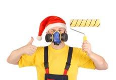 Arbetare i gasmask och santa hatt med rullen Royaltyfria Bilder