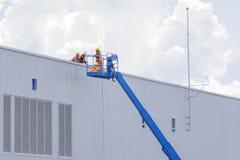 Arbetare i korgar installerar arket som bygger en fabrik Royaltyfria Foton