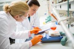Arbetare i labb som justerar mäta instrumentet Arkivbild