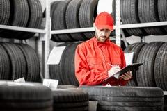 Arbetare i lagret med bilgummihjul fotografering för bildbyråer