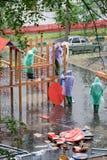 Arbetare i mång--färgade regnuddar arbetar på lekplatsen Royaltyfri Bild