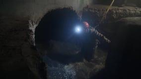Arbetare i mörk stadskloak med stort vattenflöde stock video