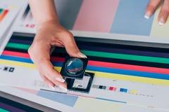 Arbetare i printing och centar bruk för press ett förstoringsglas royaltyfri bild