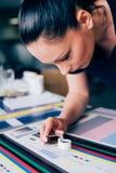 Arbetare i printing och centar bruk för press ett förstoringsglas royaltyfri foto