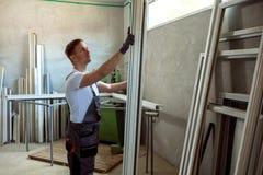 Arbetare i seminariet för framställning av av PVC-fönster och dörrar Arkivbilder
