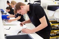 Arbetare i teknikfabrik som kontrollerar del- kvalitet Arkivfoto
