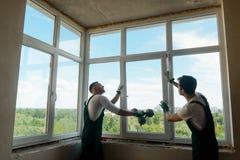 Arbetare installerar ett fönster royaltyfria bilder