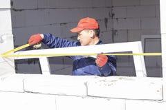 Arbetare installerar f?nsterrutor i ett hus under konstruktion arkivfoton