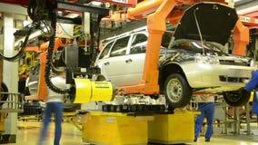 Arbetare installerar hjulen på bilen Lada Kalina av fabriken AutoVAZ