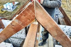 Arbetare klippte taksparrarna på taket av chainsawhuset royaltyfri fotografi