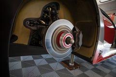 Arbetare kontrollerar de bakre bromsarna av en supercar i garaget royaltyfri illustrationer