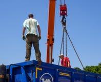 Arbetare lastar av lastbilen vid kranen Arkivbild