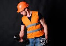 Arbetare leverantör, byggmästare på upptagen framsida med muskulös biceps Byggmästare i hjälm som utarbetar som utbildar Man i hj Royaltyfria Bilder