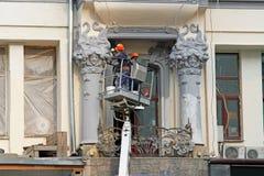 Arbetare målar kolonner med stuckaturen på fasaden av huset på Tverskaya i Moskva Arkivbild