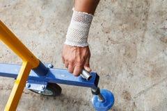 Arbetare med den förband handen på arbete Royaltyfri Fotografi