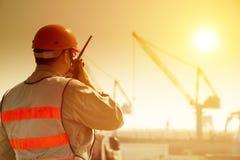Arbetare med den stora kranplatsen Royaltyfri Bild