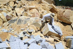 Arbetare med försök för delare förestående att dela stenen Royaltyfria Bilder