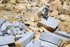 Arbetare med försök för delare förestående att dela stenen Arkivbild