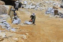 Arbetare med försök för delare förestående att dela stenen Arkivfoton