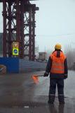 Arbetare med flaggaanseende över vägen som förhindrar trafik i konstruktionsområde Arkivfoto