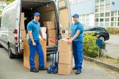 Arbetare med kartonger i Front Of Truck Royaltyfri Fotografi